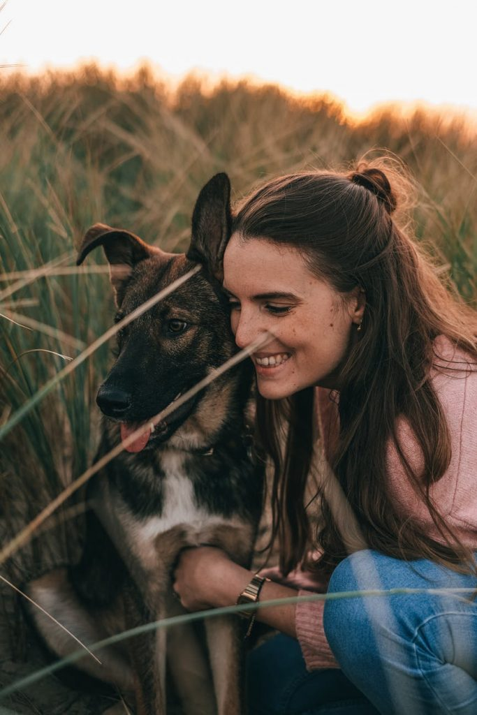 positive young woman embracing purebred dog in field